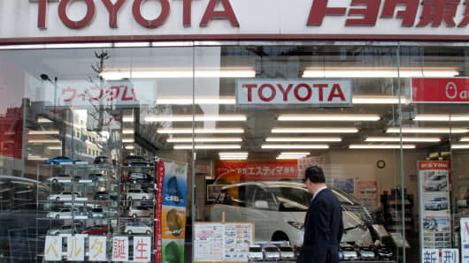 A man walks past a Toyota dealership in Tokyo, Japan.