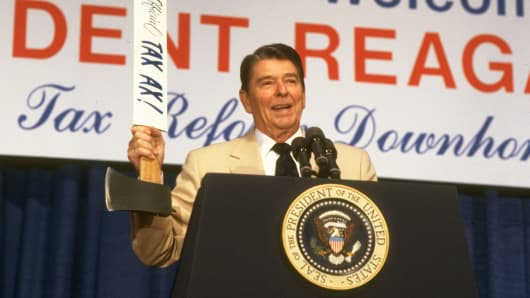 "President Ronald Reagan holding up an ax emblazoned with ""The Official TAX AX!"" at a speech in 1986."