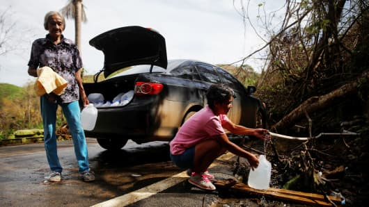 People affected by Hurricane Maria fill up water jugs from a mountain drain near the municipality of Morovis, outside San Juan, Puerto Rico, October 10, 2017.
