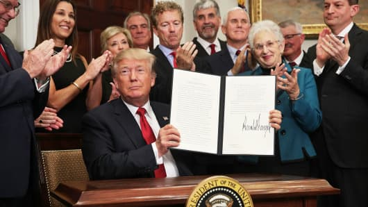 President Donald Trump shows an executive order after he signed it as Sen. Rand Paul (R-KY), Vice President Mike Pence, Rep. Virginia Foxx (R-NC) and Secretary of Labor Alexander Acosta look on during an event in the Roosevelt Room of the White House October 12, 2017 in Washington, DC.