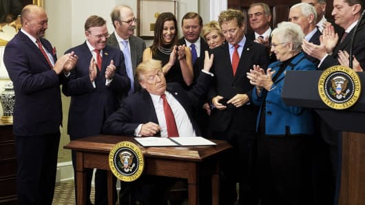 President Donald Trump pats the shoulder of Senator Rand Paul, a Republican from Kentucky, signing an executive order on health care in the Roosevelt Room of the White House in Washington, D.C., U.S., on Thursday, Oct. 12, 2017.