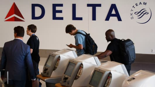 Delta Air Lines Inc. signage is displayed as a traveler uses self check-in kiosk in Delta Air Lines Inc.