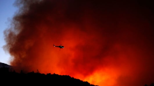 A helicopter prepares to drop water on a fire that threatens the Oakmont community along Highway 12 in Santa Rosa on October 13, 2017.