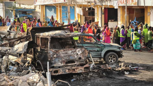 People gather near burnt vehicles a day after a truck bomb exploded in the center of Mogadishu on October 15, 2017.