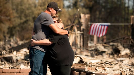 Charlie and Kate Higgins embrace in front of their burned home in Santa Rosa, California on October 12, 2017.