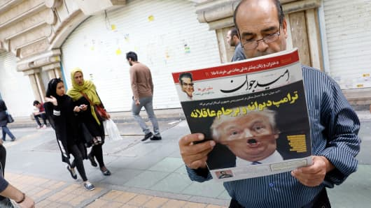 An Iranian man reads a copy of the daily newspaper 'Omid Javan' bearing a picture of US President Donald Trump with a headline that reads in Persian 'Crazy Trump and logical JCPOA (Joint Comprehensive Plan of Action)', on October 14, 2017, in front of a kiosk in the capital Tehran.