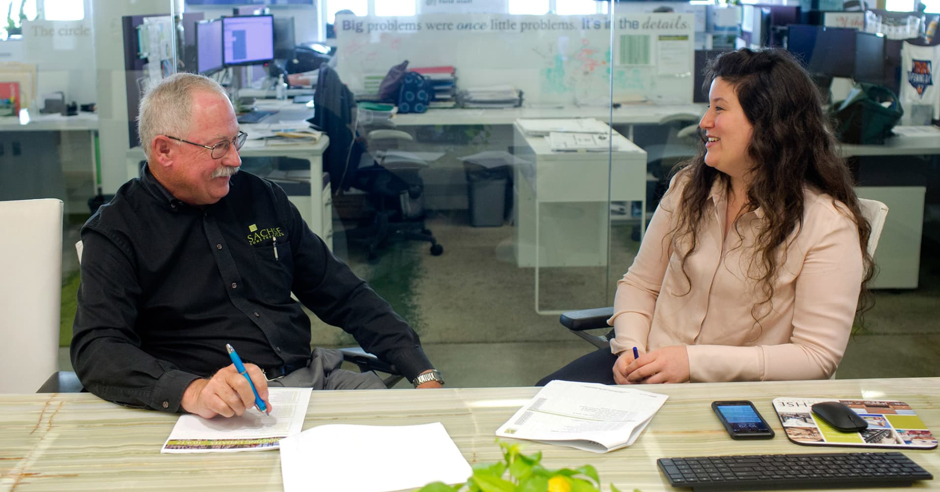 Jim Jehle, 66, a senior project manager, meets with his mentor, Nicole Mancino, 27, the director of marketing, at Sachse Construction's office in Detroit, Oct. 9, 2017.
