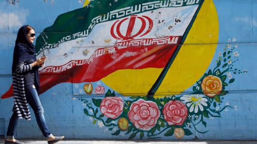 An Iranian woman walks past a mural of the Iranian flag in the capital Tehran, on October 14, 2017.
