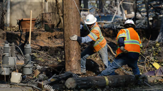 PG&E workers work to repair power lines in the Coffey Park neighborhood following the damage caused by the Tubbs Fire on October 13, 2017 in Santa Rosa, California.