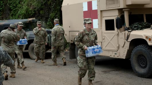Soldiers assigned to the 1st Mission Support Command, U.S. Army Reserve, move cases of bottled water while working to clear roads of debris near Adjuntas, Puerto Rico, on Saturday, Oct. 7, 2017.