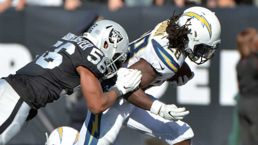 Melvin Gordon #28 of the Los Angeles Chargers scores a six-yard touchdown against the Oakland Raiders during their NFL game at Oakland-Alameda County Coliseum on October 15, 2017 in Oakland, California.