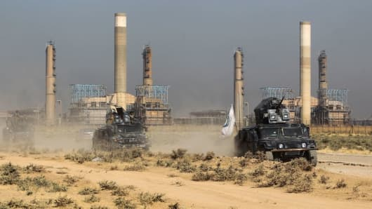 Iraqi forces drive past an oil production plant as they head towards the city of Kirkuk on October 16, 2017.