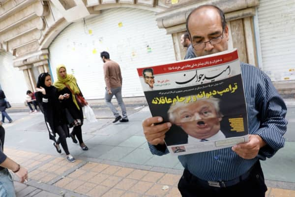 An Iranian man reads a newspaper on October 14, 2017. U.S. President Donald Trump is on the front page following news that he has decertified a nuclear deal between the two countries and others.