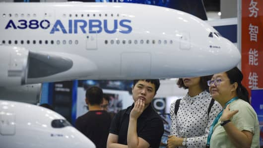 Visitors look at models of an Airbus A380 and an Airbus A350 plane at the Beijing International Aviation Expo in Beijing on September 19, 2017.