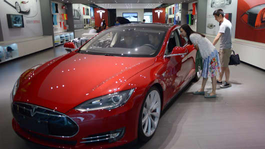 People look at a Tesla car at a company showroom in Beijing.