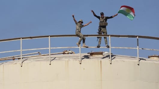 Iraqi government forces remove a Kurdish flag from the Bai Hassan oil field, west of the multi-ethnic northern Iraqi city of Kirkuk, on October 17, 2017.
