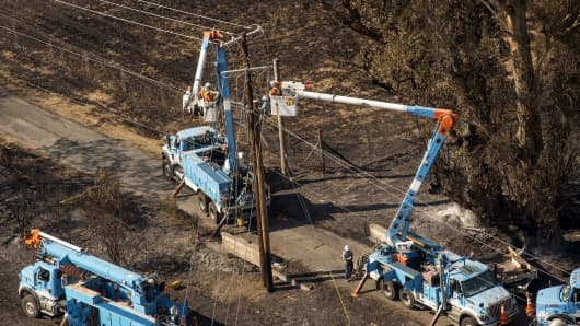 Pacific Gas & Electric Co. (PG&E) employees work to fix downed power lines burned by wildfires in this aerial photograph taken above Santa Rosa, California, Oct. 12, 2017.