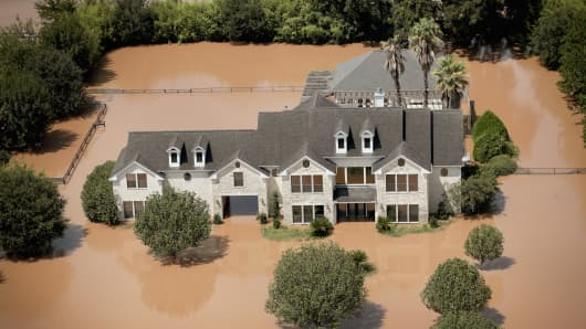 A home is surrounded by floodwater after torrential rains pounded Southeast Texas following Hurricane and Tropical Storm Harvey on August 31, 2017 near Sugar Land, Texas.