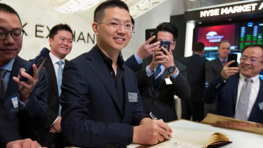 Qudian Inc. CEO Min Luo, center, signs the New York Stock Exchange guest book to celebrate his company's IPO, Wednesday, Oct. 18, 2017.