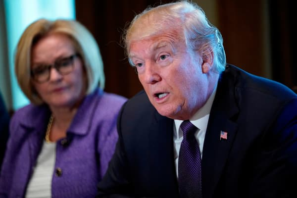 President Donald Trump (R) speaks next to Senator Claire McCaskill (D) of Missouri during a meeting with members of the the Senate Finance Committee in the Cabinet Room at the White House in Washington, DC, on October 18, 2017.
