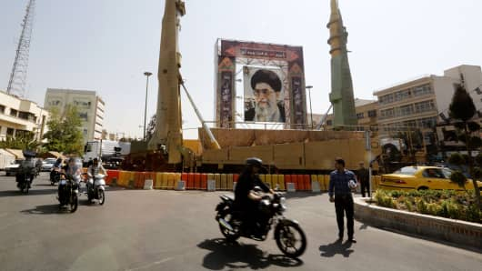 Iranians walk past Sejjil (L) and Qadr-H medium range ballistic missiles displayed next to a portrait of Iranian Supreme Leader Ayatollah Ali Khamenei on September 25, 2017, on Baharestan square in Tehran.
