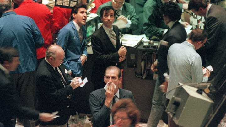 trader (c) on the New York Stock Exchange gathers his thoughts 16 October 1987 as the Dow Jones Industrial Average dropped a record 108. 36 in one day trading record.