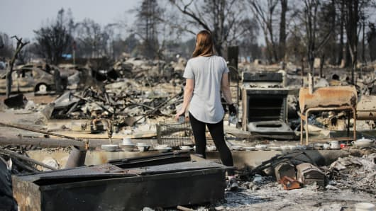 A woman looks out at the destruction caused by the Tubbs fire while holding items of emotional importance salvaged from her childhood home in the Coffey Park neighborhood on October 15, 2017 in Santa Rosa, California.