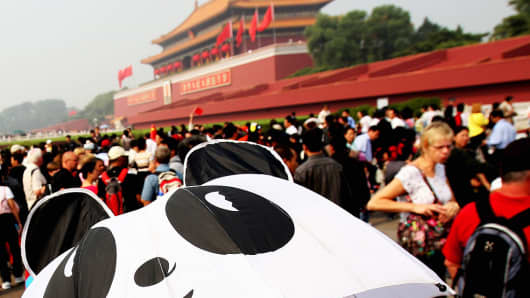 A tourist guide holds an umbrella featuring a panda pattern in front of Tiananmen Gate in Beijing, China.