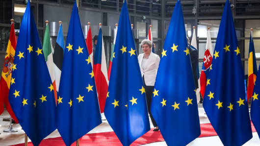 Britain's Prime Minister Theresa May walks behind flags of Europe as she arrives on the second day of a summit of European Union (EU) leaders and focusing on globalisation and migration, after the first day was dominated by the future of the EU and the Brexit, on June 23, 2017 in Brussels.