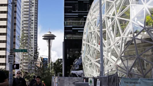 In this Oct. 11, 2017, photo, large spheres take shape in front of an existing Amazon building and in view of the Space Needle in Seattle.