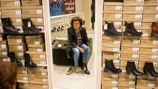 Anca Mariana Petculescu, a 64-year-old retiree, tries on a pair of boots at a mall in Bucharest, Romania.