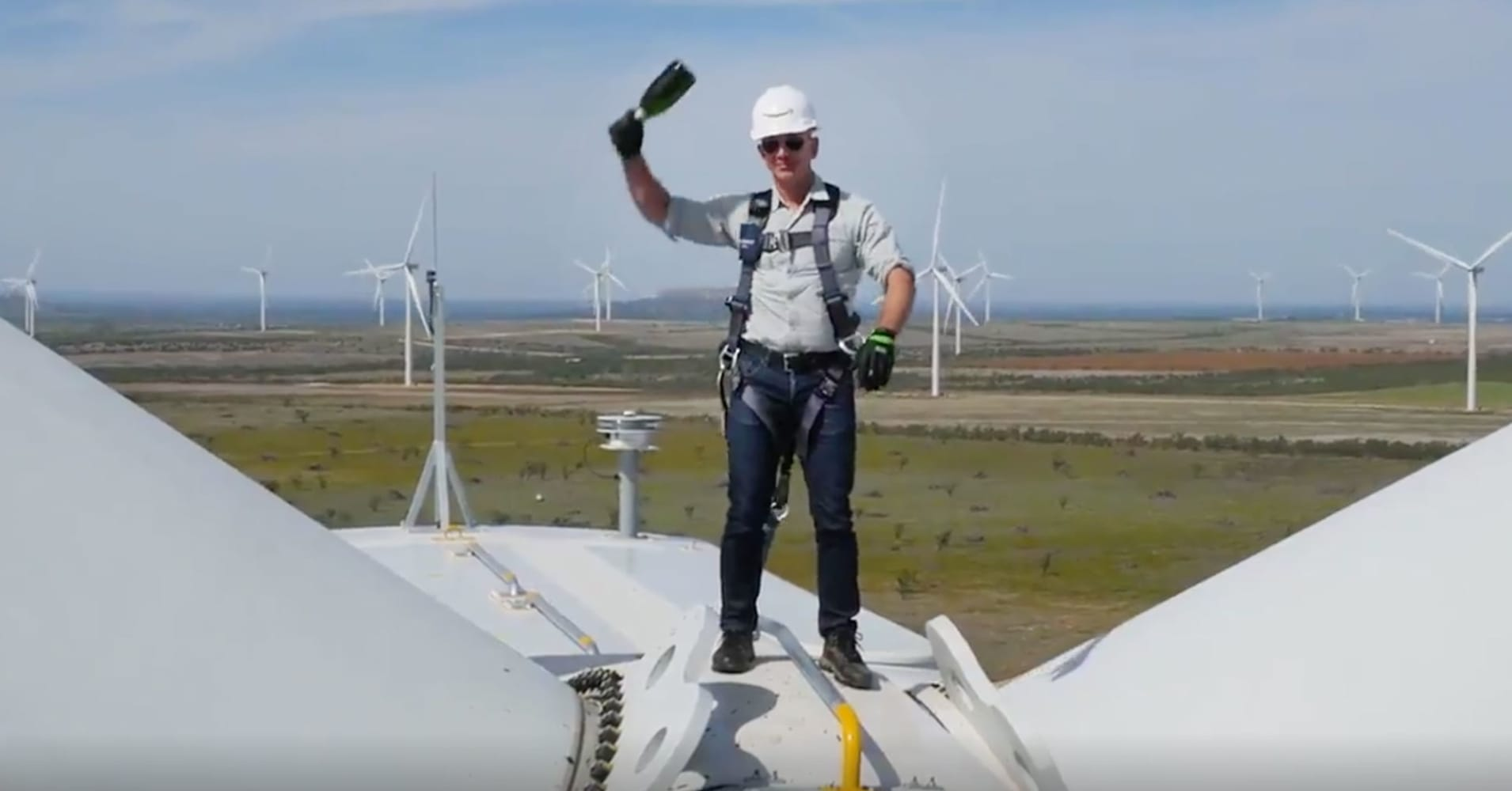 In a still from a video, Jeff Bezos christening Amazon's new wind farm.