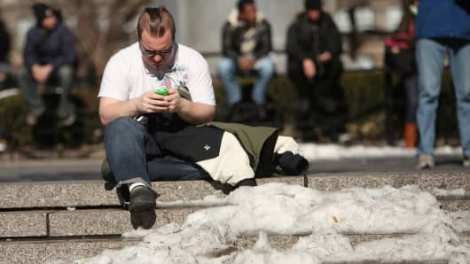 A man enjoys the warm weather while sitting in Union Square in New York City.