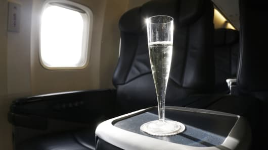 A glass of champagne sits on a tray table in the cabin of a corporate jet on Tuesday, April 12, 2016.