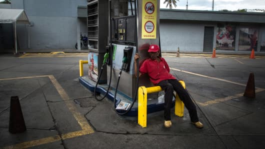An attendant sits at a closed Petroleos de Venezuela SA (PDVSA) gas build in Caracas, Venezuela, on Friday, Sept. 22, 2017.