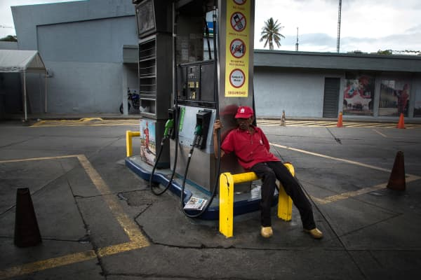 An attendant sits at a closed Petroleos de Venezuela SA (PDVSA) gas station in Caracas, Venezuela, on Friday, Sept. 22, 2017.