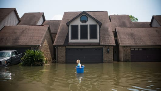 Jenna Fountain carries a bucket down Regency Drive to try to recover items from their flooded home in Port Arthur, Texas, September 1, 2017.