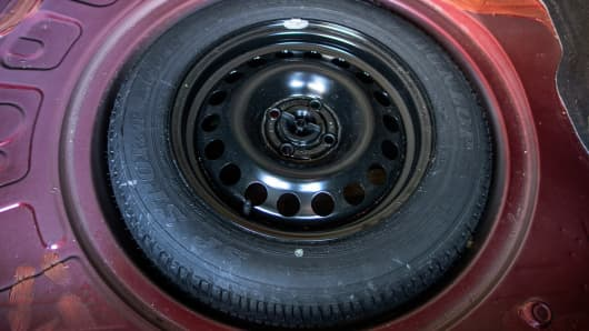 Full size spare tire stowed in trunk of car.