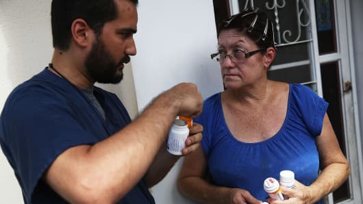 Joel Munoz Coreano, MD, helps Melba Tirado with her medication as he checks in on hurricane survivors who are cutoff from easy access to medical aid in the wake of the devastation left across the island by Hurricane Maria on October 5, 2017 in Utuado, Puerto Rico.
