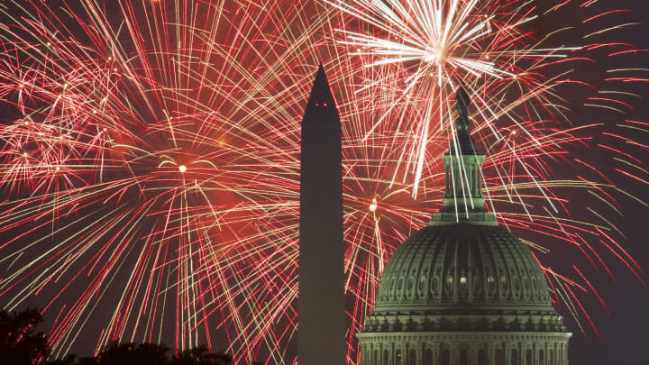 Fireworks explode over the National Mall as the US Capitol (R) and National Monument.