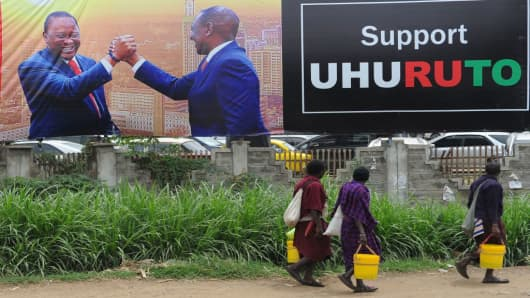 Pedestrians walk past a campaign poster of Kenya's President Uhuru Kenyatta and Deputy-President William Ruto in the capital Nairobi on October 23, 2017.