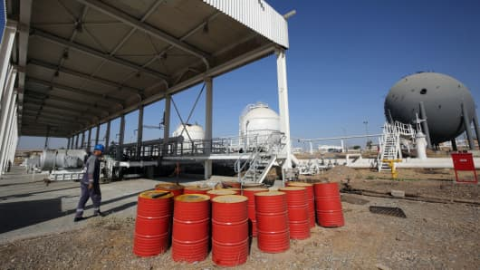 An employee walks past oil barrels at the Bai Hassan oil field, west of the multi-ethnic northern Iraqi city of Kirkuk, on October 19, 2017.