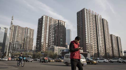 A pedestrian crosses a road in front of residential buildings in Beijing, China.