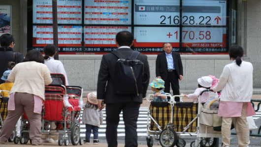 Pedestrians stand in front of an electronic stocks indicator displaying share prices of the Tokyo Stock Exchange in Tokyo on Oct. 23, 2017.