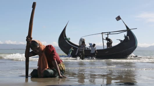 A woman collapses from exhaustion as Rohingya refugees arrive by a wooden boat from Myanmar to the shore of Shah Porir Dwip, in Teknaf, near Cox's Bazar in Bangladesh, October 1, 2017
