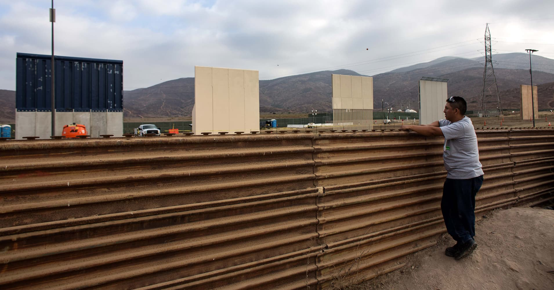 A man watches across the border from Tijuana, Mexico, on October 12, 2017 a prototype of US President Donald Trump's US-Mexico border wall being built near San Diego, in the US, Following up on President Donald Trump's campaign promise to build a wall along the entire 3,200 kilometre (2,000 mile) Mexican frontier, the Department of Homeland Security began building prototypes for the barrier along the border in San Diego and Imperial counties, as it announced in August.