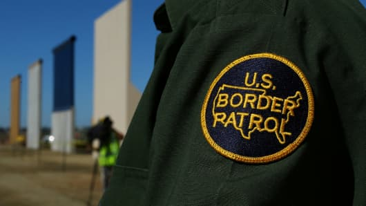 A border patrol officer stands next to some of U.S. President Donald Trump's eight border wall prototypes as they near completion along U.S.- Mexico border in San Diego, California.