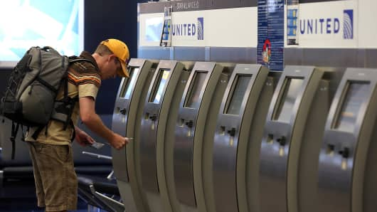 A United Airlines passenger gets boarding documents from a kiosk at San Francisco International Airport.