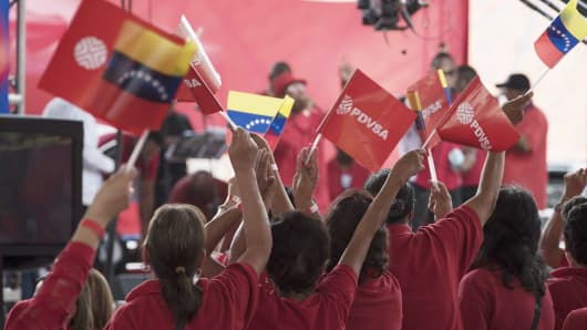 Employees of Petroleos de Venezuela SA (PDVSA) wave flags during a swearing in ceremony for the new board of directors of Venezuela's state oil company in Caracas, Venezuela, on Tuesday, Jan. 31, 2017.