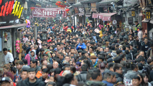 Tourists swarm into the main street of the ancient town of Ciqikou on January 30, 2017 in Chongqing, China.